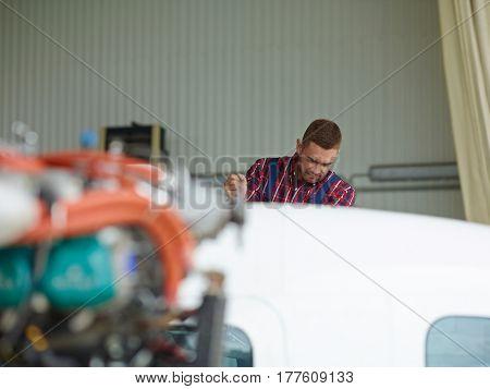 Technician repairing engine of jet before season of flights