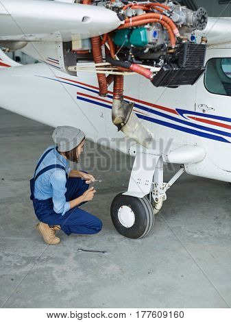 Female worker serving jetliner and checking its condition