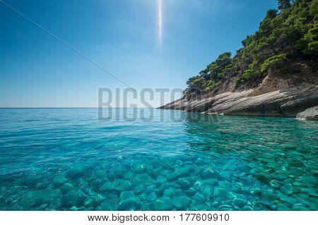 Clear blue sea off a rocky coastline.