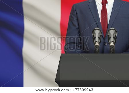 Businessman Or Politician Making Speech From Behind A Pulpit With National Flag On Background - Fran