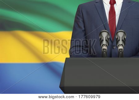 Businessman Or Politician Making Speech From Behind A Pulpit With National Flag On Background - Gabo