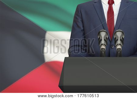 Businessman Or Politician Making Speech From Behind A Pulpit With National Flag On Background - Kuwa