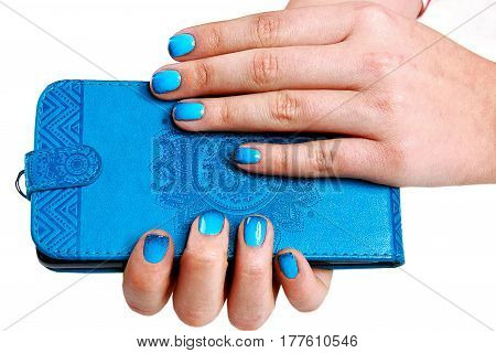 A girl holds in hands with bright blue manicure mobile phone in phone case (cover)