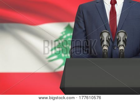 Businessman Or Politician Making Speech From Behind A Pulpit With National Flag On Background - Leba