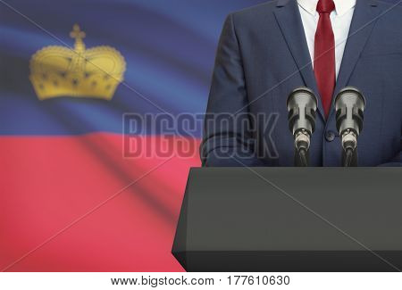 Businessman Or Politician Making Speech From Behind A Pulpit With National Flag On Background - Liec