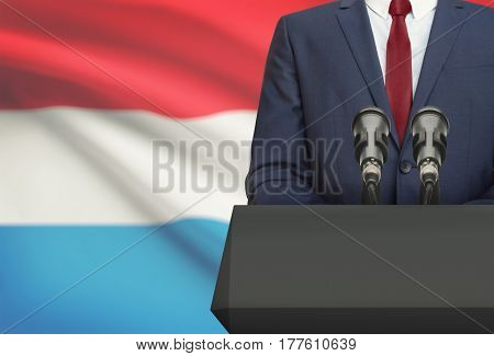 Businessman Or Politician Making Speech From Behind A Pulpit With National Flag On Background - Luxe