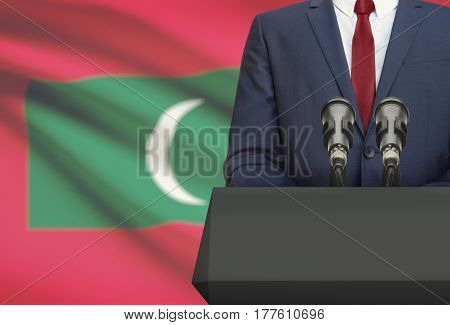 Businessman Or Politician Making Speech From Behind A Pulpit With National Flag On Background - Mald