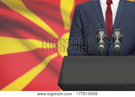 Businessman Or Politician Making Speech From Behind A Pulpit With National Flag On Background - Mace