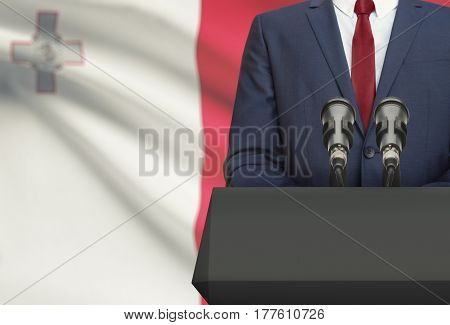 Businessman Or Politician Making Speech From Behind A Pulpit With National Flag On Background - Malt