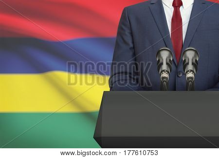 Businessman Or Politician Making Speech From Behind A Pulpit With National Flag On Background - Maur