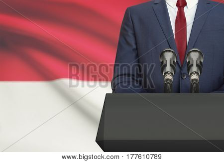 Businessman Or Politician Making Speech From Behind A Pulpit With National Flag On Background - Mona