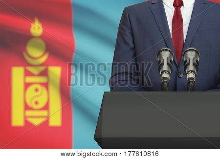 Businessman Or Politician Making Speech From Behind A Pulpit With National Flag On Background - Mong