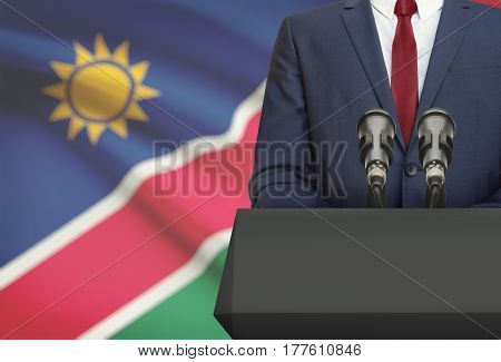Businessman Or Politician Making Speech From Behind A Pulpit With National Flag On Background - Nami