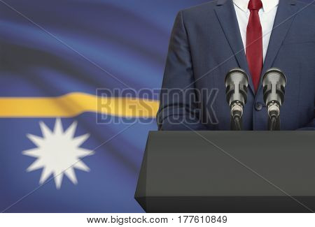 Businessman Or Politician Making Speech From Behind A Pulpit With National Flag On Background - Naur