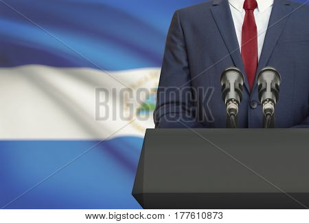 Businessman Or Politician Making Speech From Behind A Pulpit With National Flag On Background - Nica