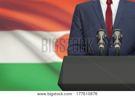 Businessman Or Politician Making Speech From Behind A Pulpit With National Flag On Background - Nige