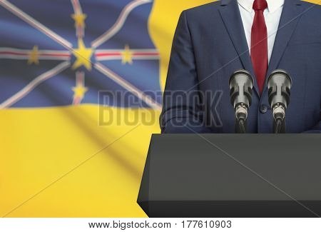 Businessman Or Politician Making Speech From Behind A Pulpit With National Flag On Background - Niue
