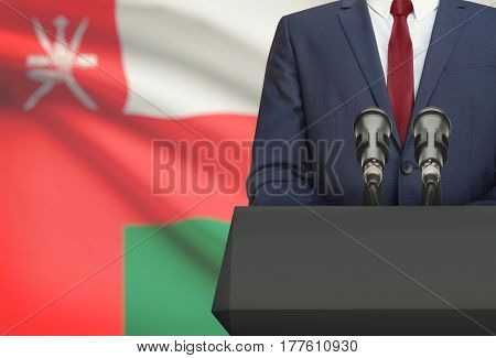Businessman Or Politician Making Speech From Behind A Pulpit With National Flag On Background - Oman