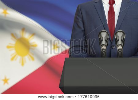 Businessman Or Politician Making Speech From Behind A Pulpit With National Flag On Background - Phil
