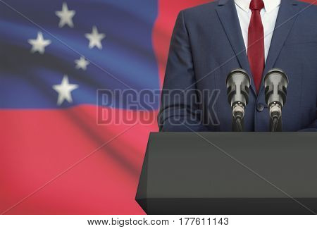 Businessman Or Politician Making Speech From Behind A Pulpit With National Flag On Background - Samo