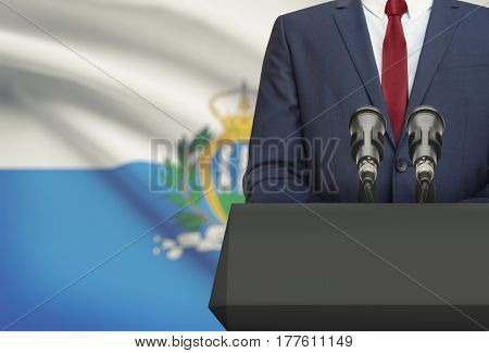 Businessman Or Politician Making Speech From Behind A Pulpit With National Flag On Background - San