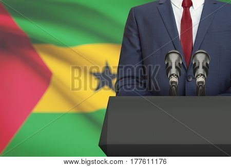 Businessman Or Politician Making Speech From Behind A Pulpit With National Flag On Background - Sao