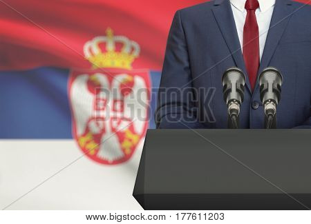 Businessman Or Politician Making Speech From Behind A Pulpit With National Flag On Background - Serb