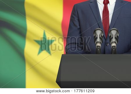 Businessman Or Politician Making Speech From Behind A Pulpit With National Flag On Background - Sene