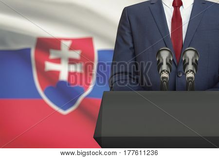 Businessman Or Politician Making Speech From Behind A Pulpit With National Flag On Background - Slov