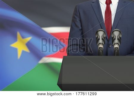 Businessman Or Politician Making Speech From Behind A Pulpit With National Flag On Background - Sout