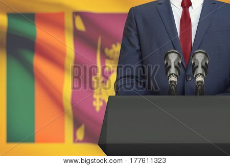 Businessman Or Politician Making Speech From Behind A Pulpit With National Flag On Background - Sri