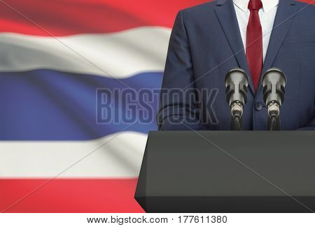 Businessman Or Politician Making Speech From Behind A Pulpit With National Flag On Background - Thai