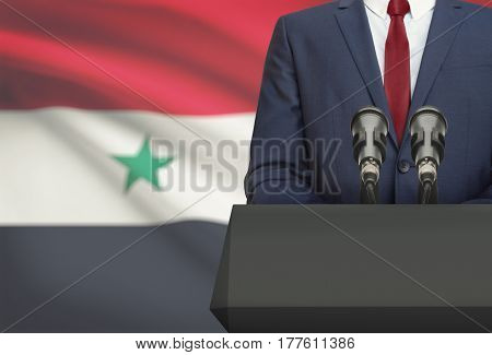 Businessman Or Politician Making Speech From Behind A Pulpit With National Flag On Background - Syri