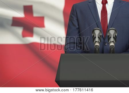 Businessman Or Politician Making Speech From Behind A Pulpit With National Flag On Background - Tong