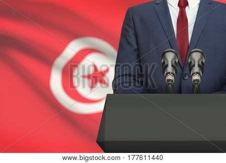 Businessman Or Politician Making Speech From Behind A Pulpit With National Flag On Background - Tuni