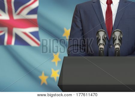 Businessman Or Politician Making Speech From Behind A Pulpit With National Flag On Background - Tuva
