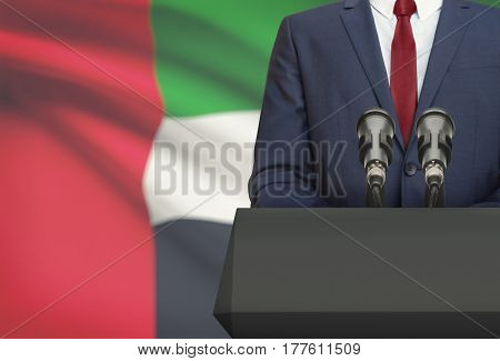 Businessman Or Politician Making Speech From Behind A Pulpit With National Flag On Background - Unit