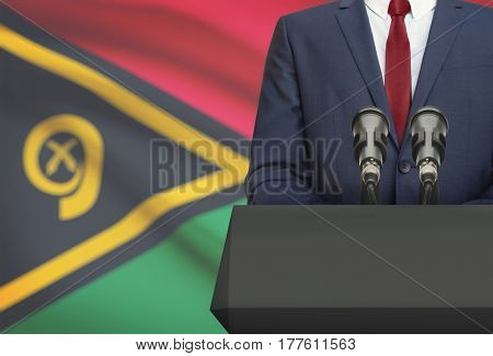 Businessman Or Politician Making Speech From Behind A Pulpit With National Flag On Background - Vanu
