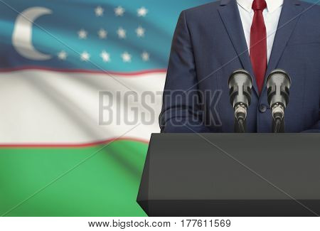 Businessman Or Politician Making Speech From Behind A Pulpit With National Flag On Background - Uzbe