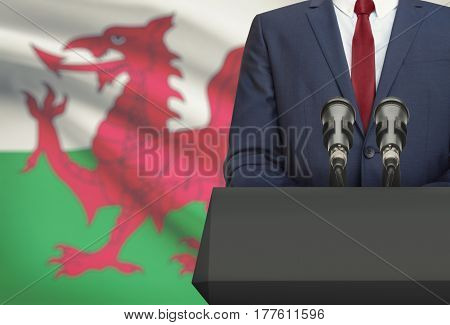 Businessman Or Politician Making Speech From Behind A Pulpit With National Flag On Background - Wale