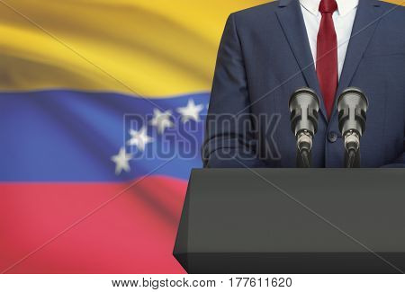 Businessman Or Politician Making Speech From Behind A Pulpit With National Flag On Background - Vene