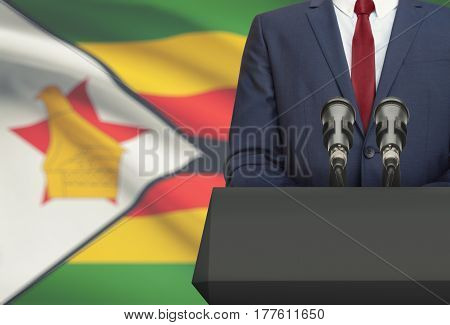 Businessman Or Politician Making Speech From Behind A Pulpit With National Flag On Background - Zimb