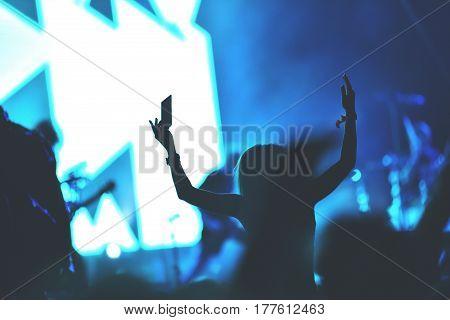 Rear View Of A Woman Enjoying A Concert