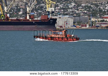 Small Ship In The Port Of The Service. Red Small Boat. Cargo Port With Port Cranes. Sea Bay And Moun