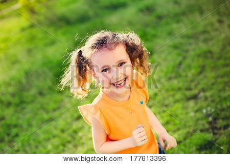 The little girl laughs. Girl running on green grass in the spring.The child's teeth fall out. Girl with two tails on the head. Soft focus