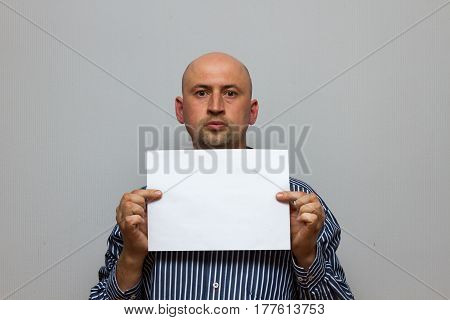 bald business man is posing with blank copy space on a gray background