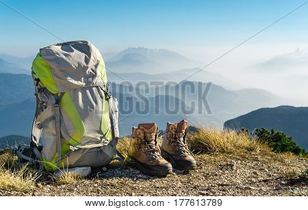 Hiking equipment. Backpack and boots on top of the mountain. Beautiful view to mountain ranges and fog filled valleys.