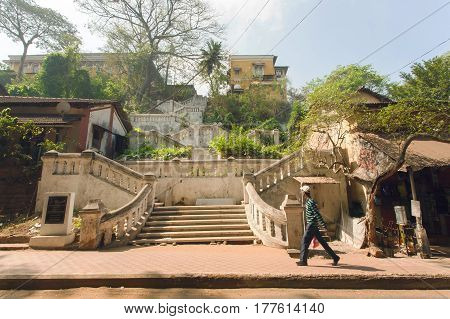 PANJIM, INDIA - MAR 1, 2017: Old and green part of town with stone retro stairs and walking people on March 1, 2017. Near 5 million tourists visit Goa annually