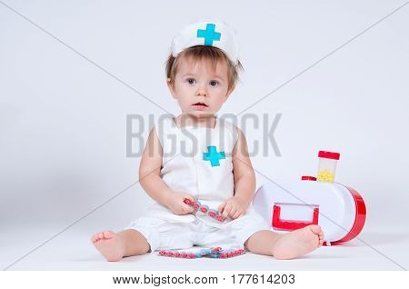 The girl laughs while playing a nurse with pills.