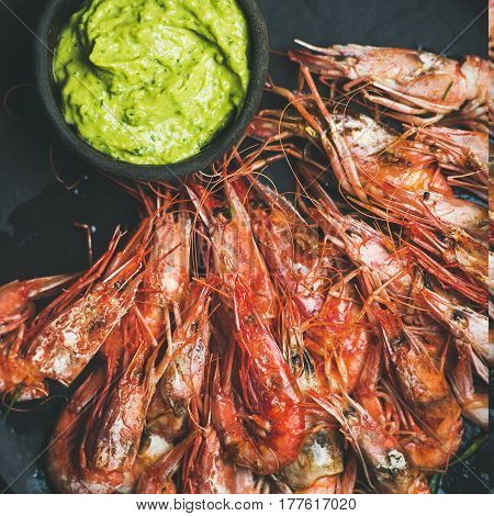 Roasted red shrimps with guacamole avocado sauce in slate stone black plate over grey concrete background, top view, square crop